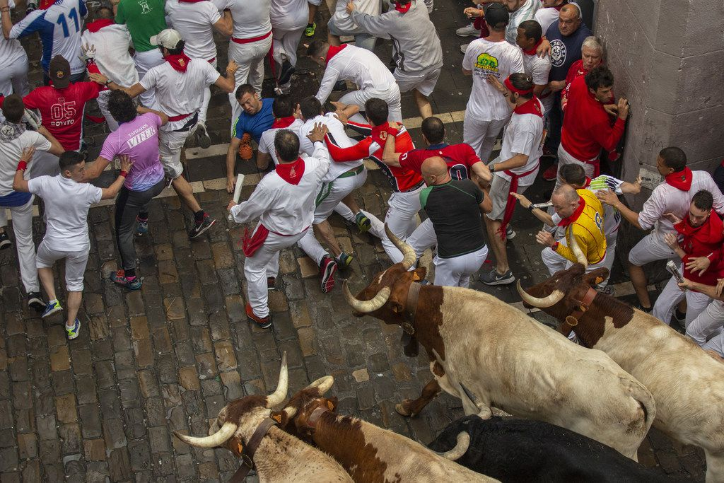 Revellers fall as they run with Puerto de San Lorenzo's fighting bulls during the second day of the San Fermin Running of the Bulls festival.