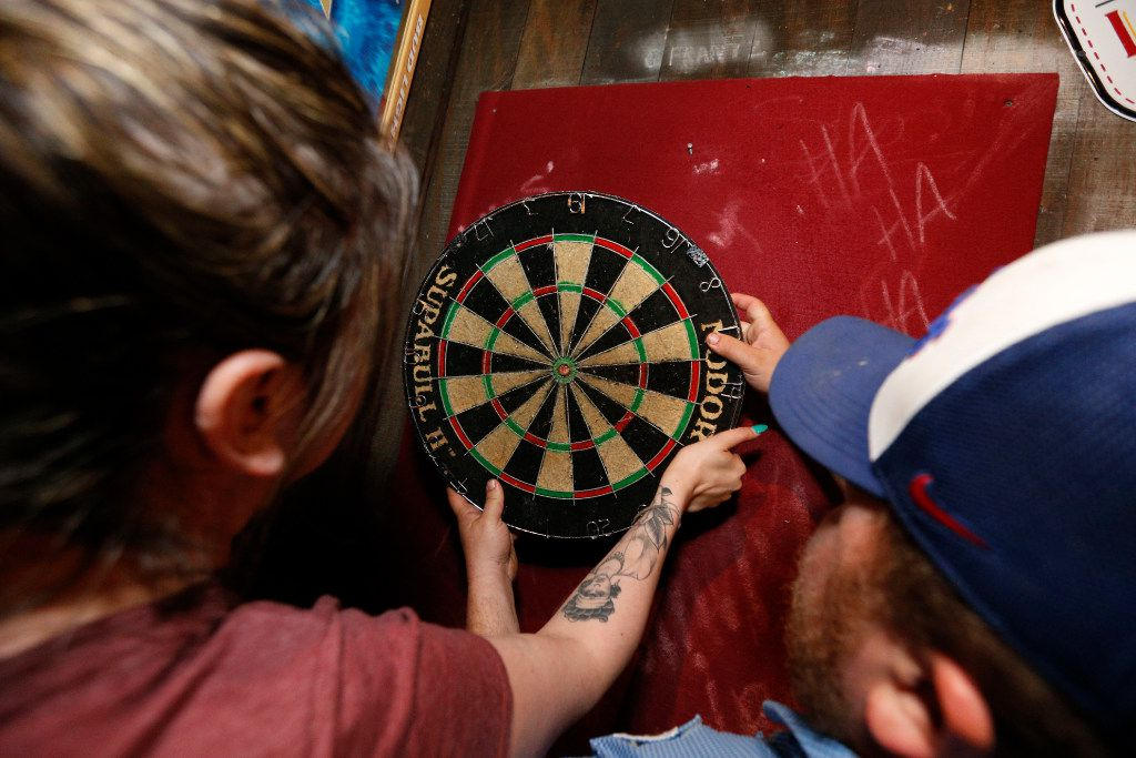 Workers place the dart board back on the wall after someone tried to walk out with it during the last hours of operation of the Elbow Room in Dallas on April 16, 2017. (Nathan Hunsinger/The Dallas Morning News)