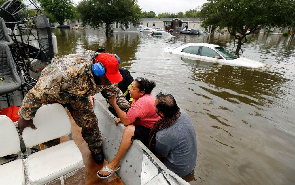 Gulf Coast Rescue Squad air boat driver Felton Jones pulls LaJuana Cisneros into a boat with the assistance of her husband, Freddie, as they were rescued from their flooded home in Pearland Acres Mobile Home Community in Pearland on Sunday, Aug. 27, 2017. Tropical Storm Harvey dumped waves of rain along the southeast Texas coast and the Houston area.