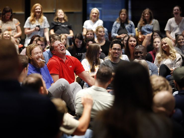 Brain Wang (center, right) and Ryan Garrahan (center, left) shared a laugh with the group during an all-staff meeting and prayer at Watermark Community Church in Dallas on Sept. 3.