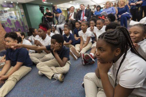 Un grupo de niños escucha atentamente el desafío de lectura del alcade.