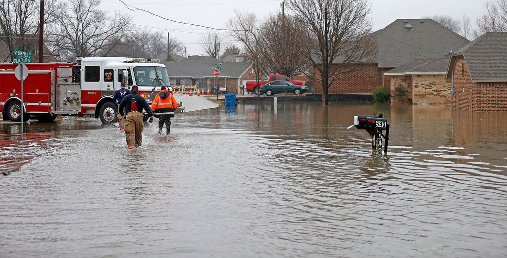 Rockwall fire department firefighters walk in the flooded water on Lakeside Drive in Rockwall, Texas, Thursday, Feb. 22, 2018.