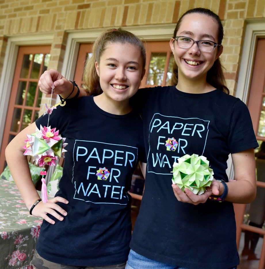 Isabelle Adams, 14, (left) and her sister Katherine Adams, 12, with origami ornaments made by volunteers for their organization Paper For Water, at their home in Dallas, July 24, 2018. Since the organization was launched, the young sisters have worked with hundreds of volunteers to raise more than $1.3 million to help fund 150 plus water projects in 14 countries.