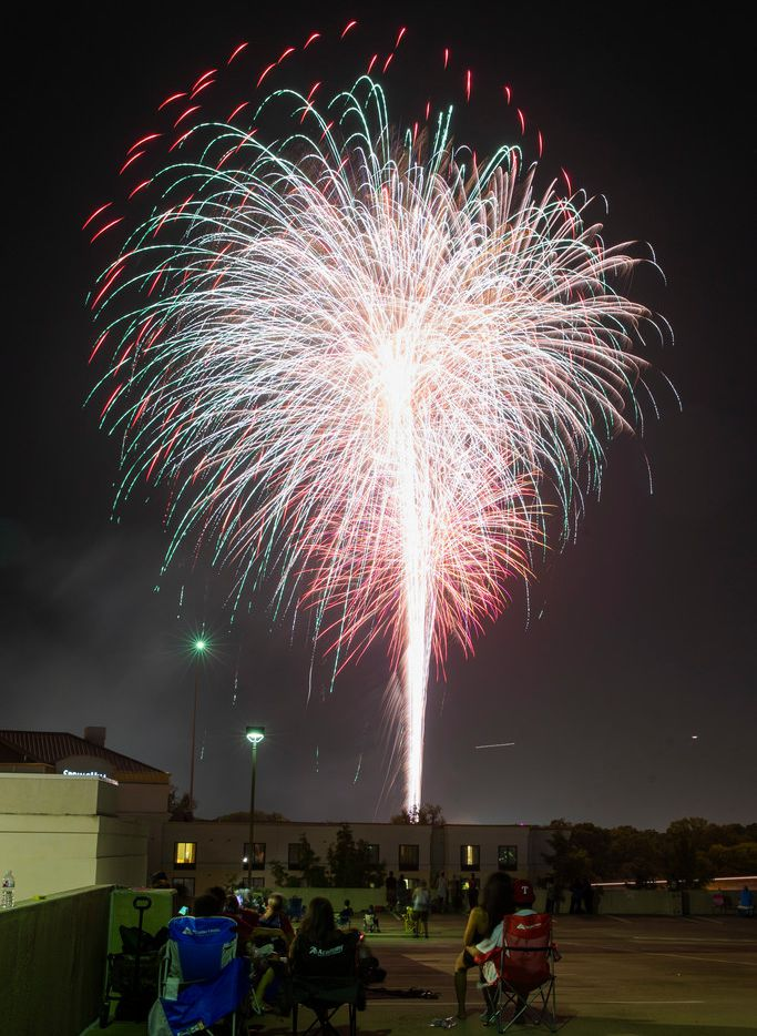 People watch fireworks from atop a parking garage Thursday at a SpringHill Suites by Marriott Fort Worth.