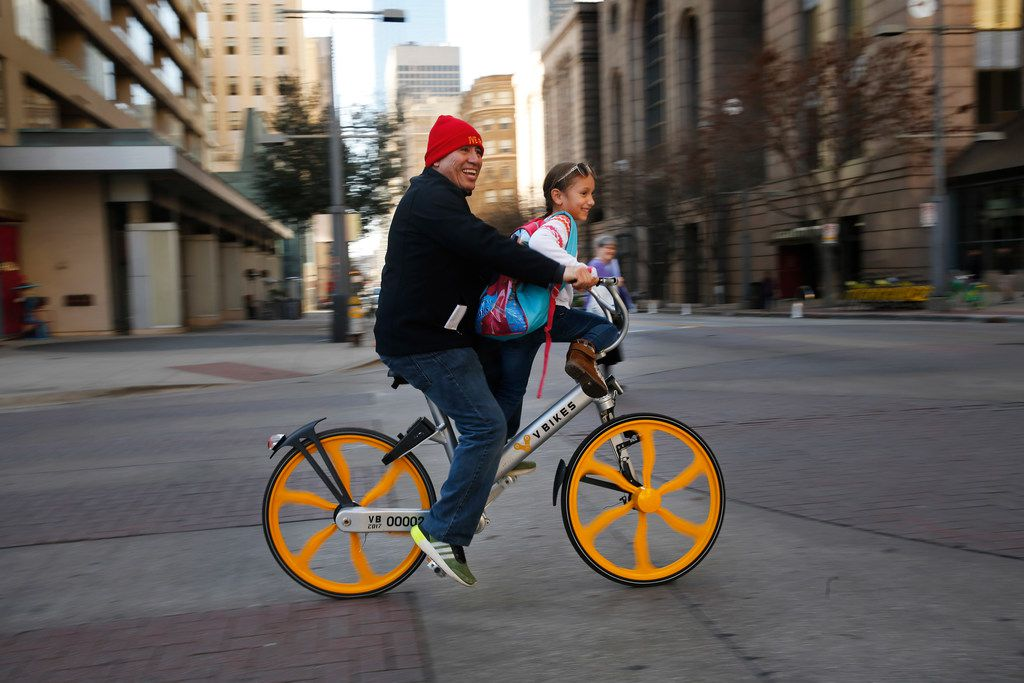 David Ramirez and his niece Giana Correa of Dallas ride a V Bikes rental bicycle along the North Texas March for Life route in downtown Dallas, Saturday, January 20, 2018.