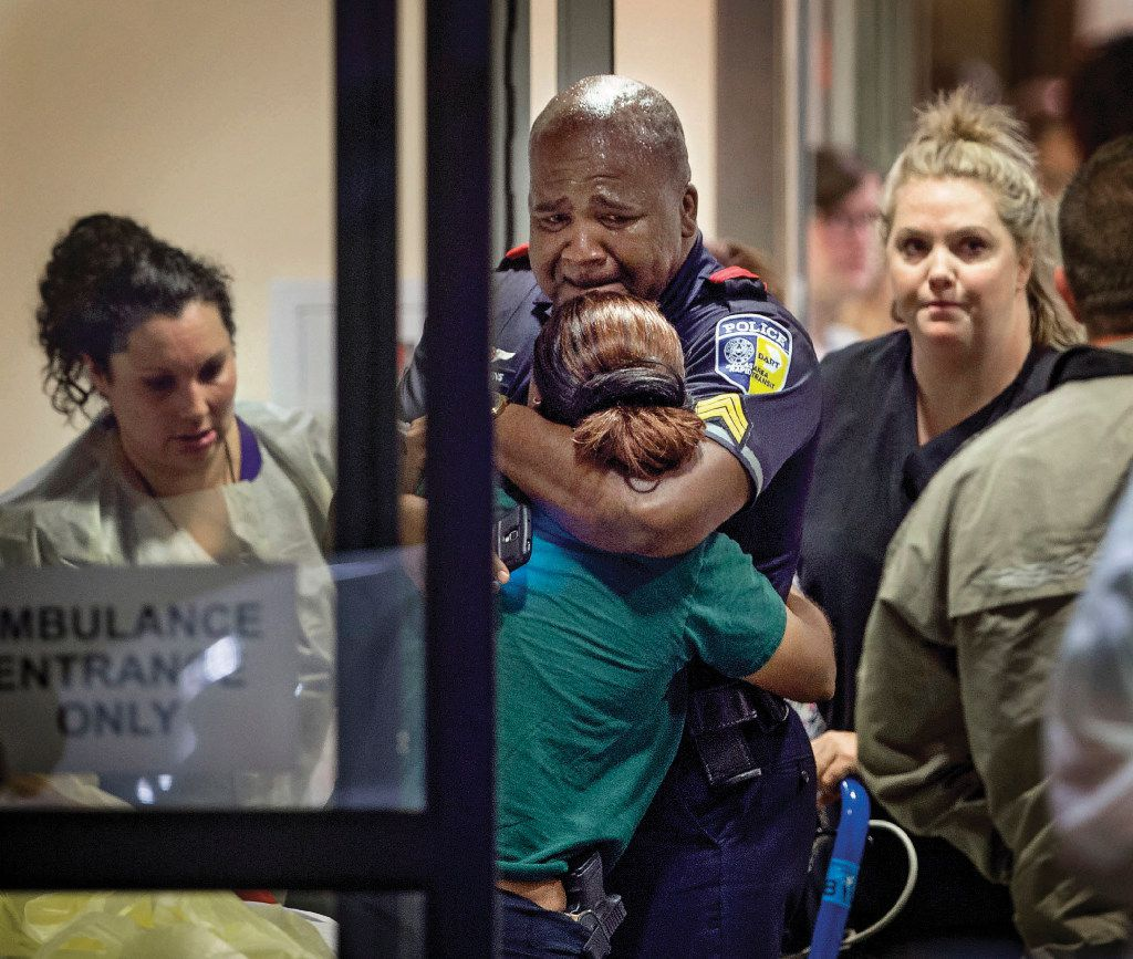 A Dallas Area Rapid Transit police officer receives comfort at Baylor University Hospital emergency room entrance on July 7, 2016, in Dallas.