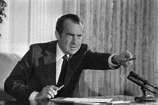 President Richard Nixon offers a souvenir pen to one of those in attendance, Dec. 23, 1971, after signing the National Cancer Act at the White House.