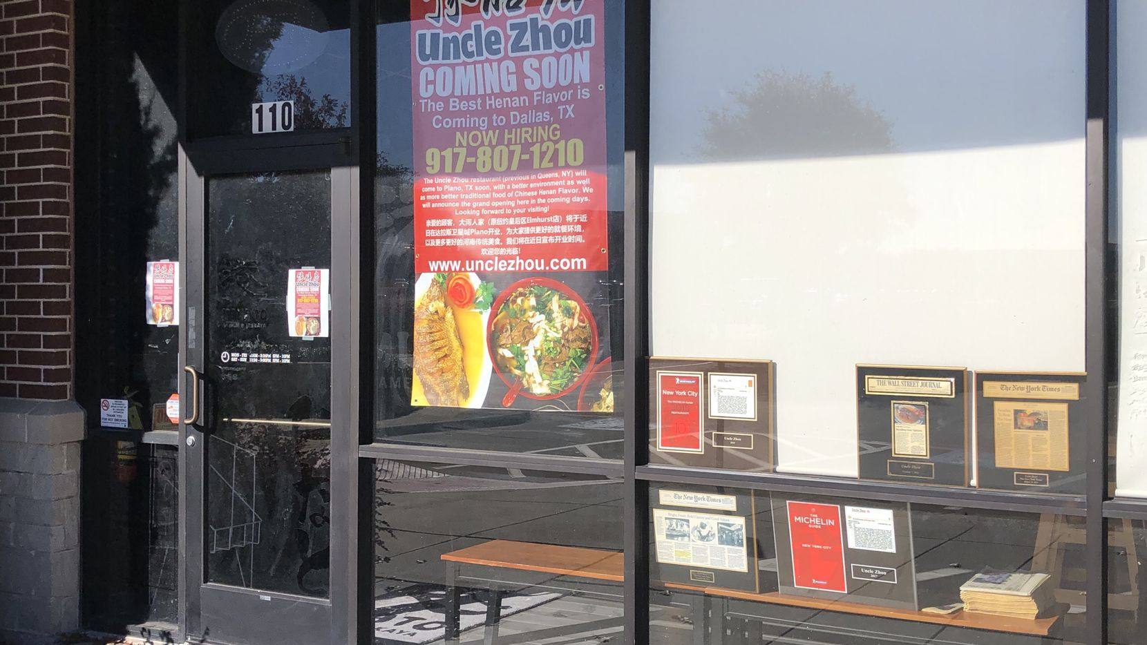 Uncle Zhou's coming-soon signs are displayed in the window of the restaurant in Plano. Owner Quan Zhou also put the restaurant's accolades on display in the windows: two stories from 'The New York Times,' two Michelin Guide write-ups and a 'Wall Street Journal' blurb.