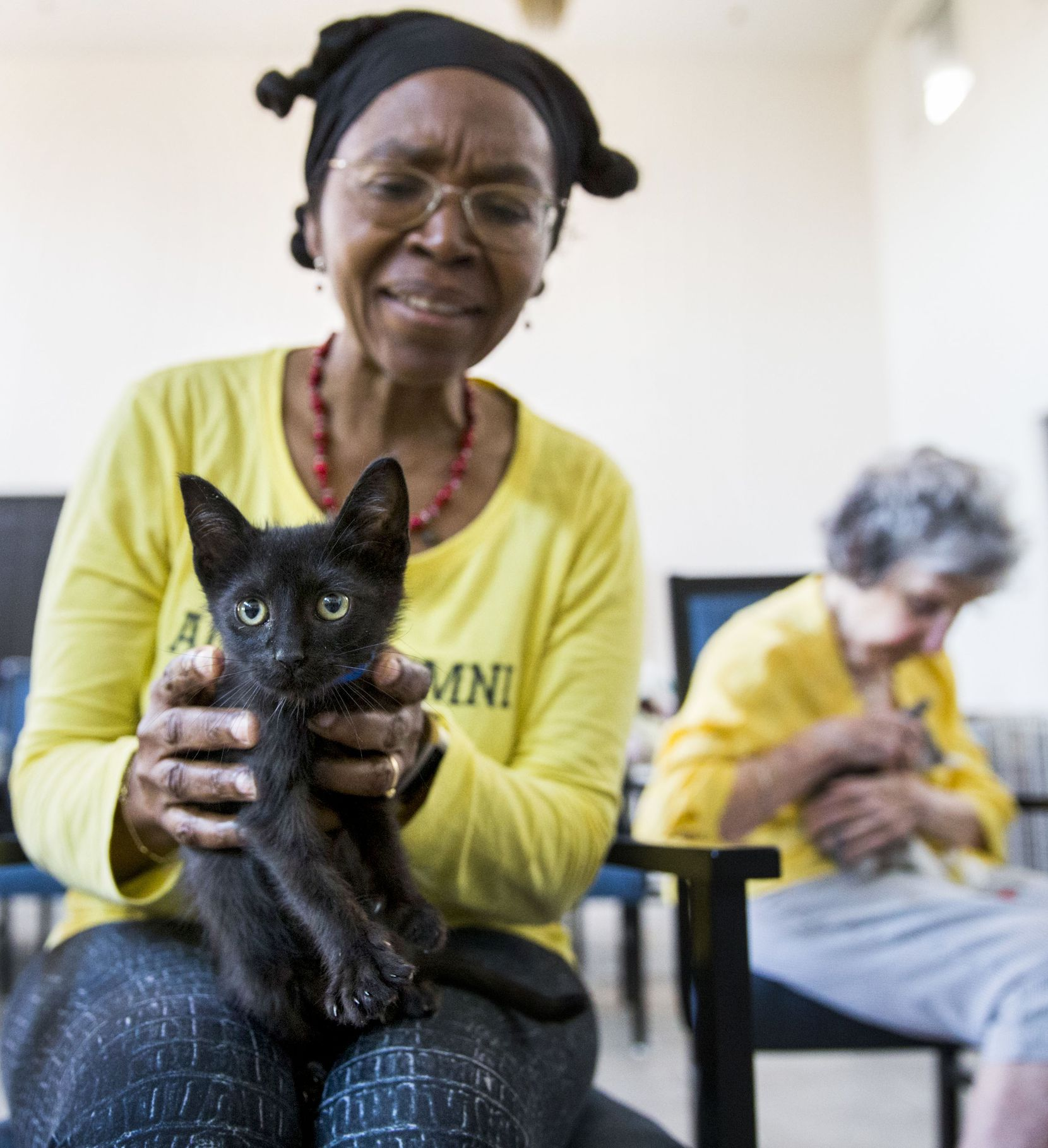 Constance Uzor (left) and Dottie Lemmond held kittens before the yoga class. The city's Prairie Paws Adoption Center has over 200 cats and kittens in need of homes.