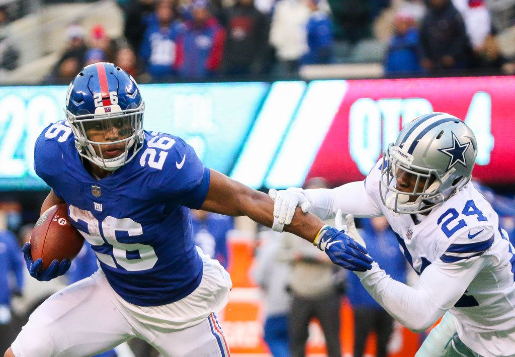 New York Giants running back Saquon Barkley (26) carrie the ball past Dallas Cowboys cornerback Chidobe Awuzie (24) in the second half of an NFL football game at MetLife Stadium in East Rutherford, New Jersey on Sunday, Dec. 30, 2018. (Shaban Athuman/The Dallas Morning News)