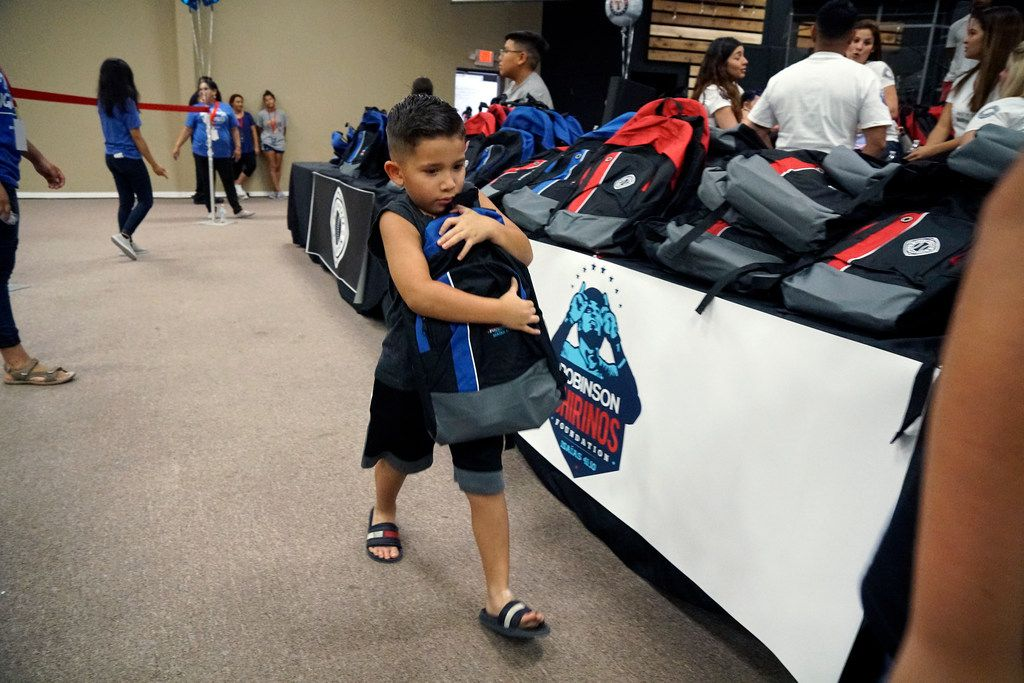 Nathaniel Ojeda (6) struggles to carry the new backpack he got at the Back to School Block Party at Refuge Church in Fort Worth, Texas on Saturday August 18, 2018. (Lawrence Jenkins/Special Contributor)