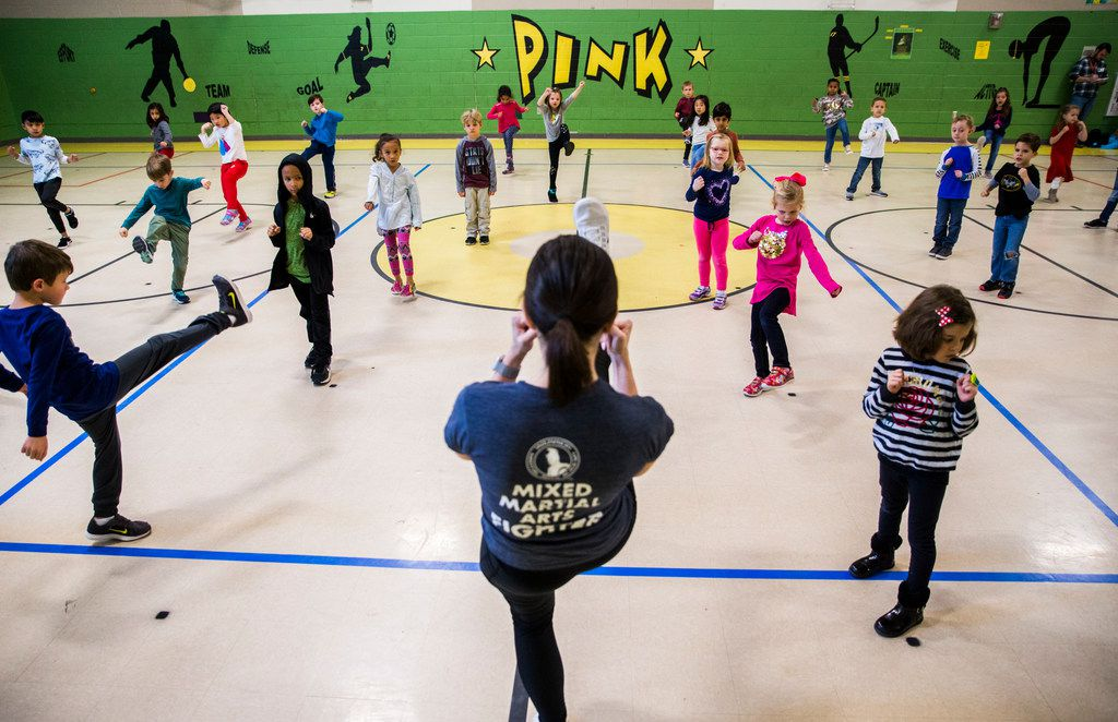 Pamela Cohen (center), owner of Warrior Martial Arts Academy, leads kindergarten students in a martial arts class at Pink Elementary in Frisco.
