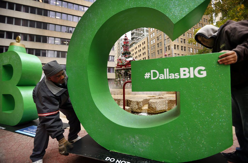 """James Reid (left) and Rogelio Gutierrez installed a Christmas-ornament letter """"G"""" at Akard and Main streets in downtown Dallas in 2013. The decorations were part of the Dallas BIG campaign."""