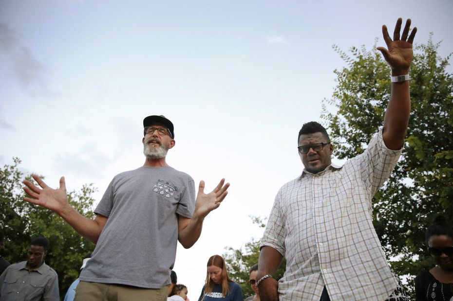Pastors Mike Connaway (left) of VLife Church and Derrick Golden of Amazing Church, both of McKinney, led a group in prayer in June 2015, after the pool party incident. (File Photo/Andy Jacobsohn)
