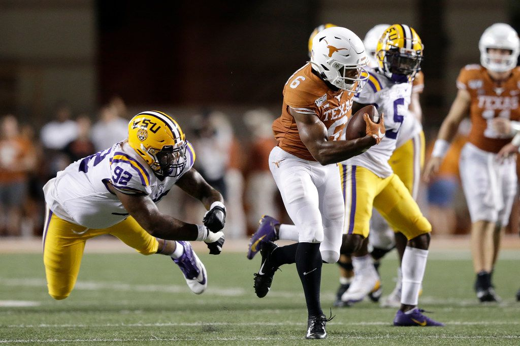 AUSTIN, TX - SEPTEMBER 07:  Devin Duvernay #6 of the Texas Longhorns breaks the tackle by Neil Farrell Jr. #92 of the LSU Tigers and runs for a touchdown in the fourth quarter at Darrell K Royal-Texas Memorial Stadium on September 7, 2019 in Austin, Texas.