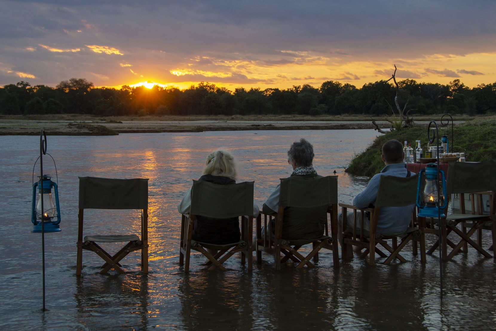 Visitors watch the sunset over the Kapamba River in Zambia's South Luangwa National Park.
