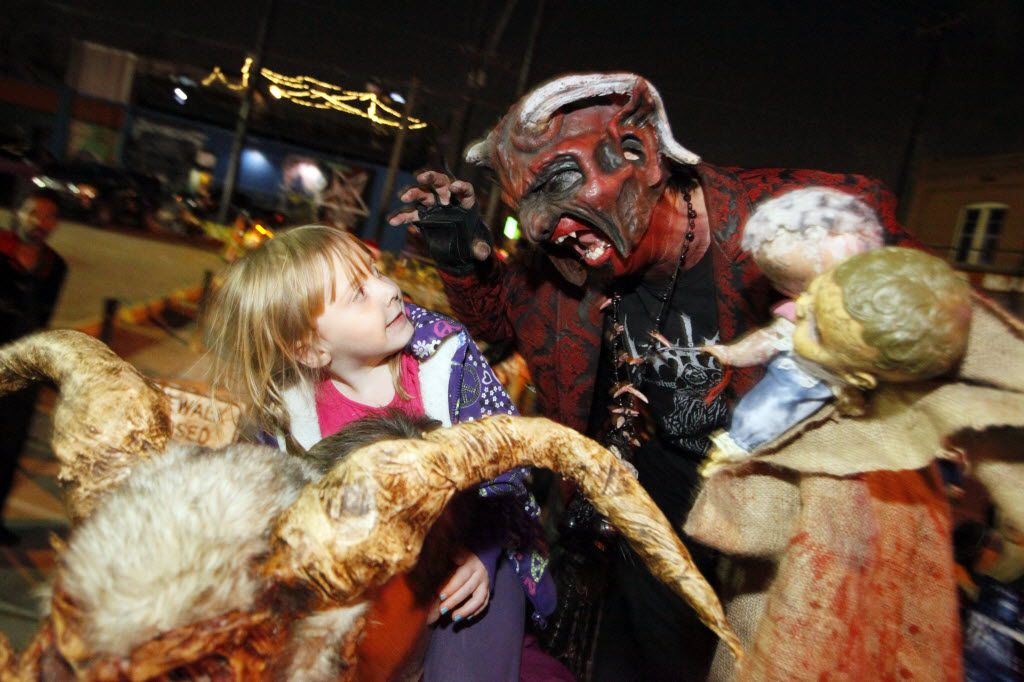 A Krampus character only known as Satan, right, attempts to scare young Natalie Ray, 3, of Plano, as she sits on the shoulders of her grandfather Eric Kristiansen, before the Dallas Krampus Walk through the streets of Deep Ellum, organized by the Krampus Society and Dark Hour Haunted House, on Friday, Dec. 5, 2014.