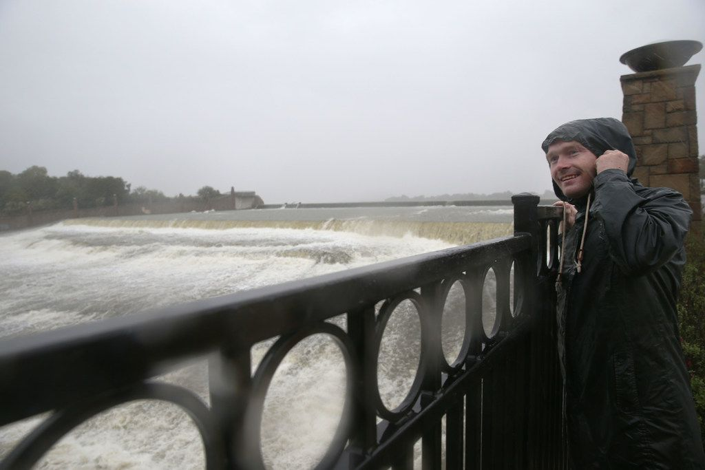 Garland resident Rocky Vanous watches water flow over White Rock Lake's spillway in Dallas on Saturday, October 13, 2018.