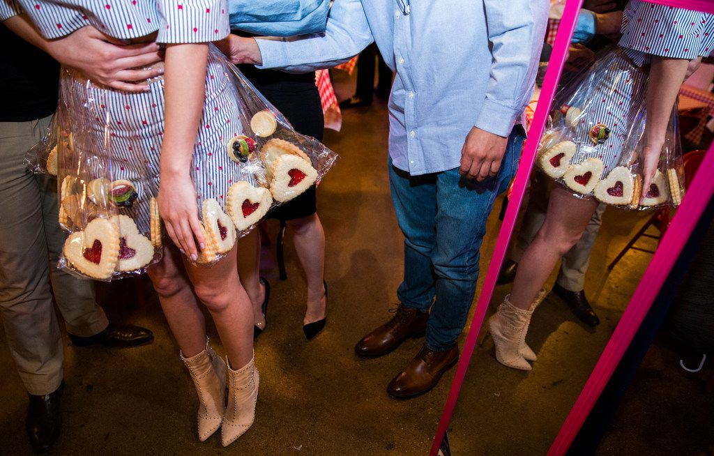 Model Aneida Gonzalez gets some help putting on a skirt adorned with cookies and fruit tarts from La Madeline before the Greater Dallas Restaurant Association's Food in Fashion event on Wednesday, February 7, 2018 at Trinity Groves in Dallas. The designer was Ivette Alvarez. (Ashley Landis/The Dallas Morning News)