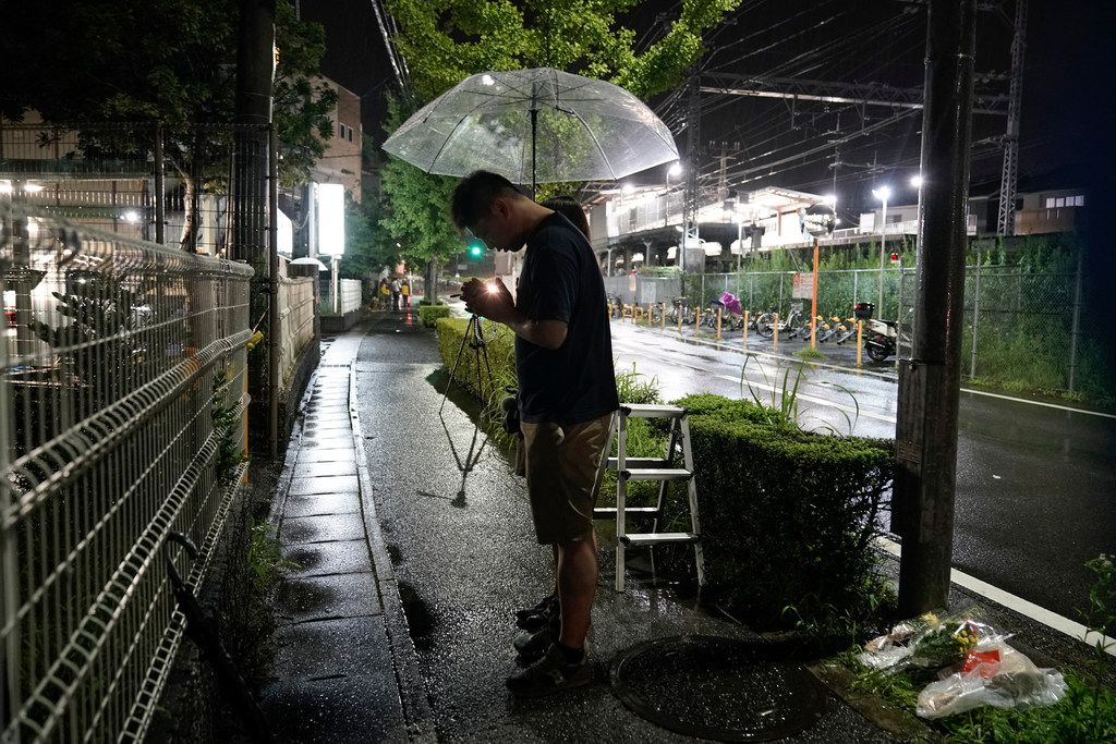 """A couple prays after placing flowers near the Kyoto Animation building, Friday, July 18, 2019, in Kyoto, Japan.   A man screaming """"You die!"""" burst into an animation studio in Kyoto, doused it with a flammable liquid and set it on fire Thursday."""