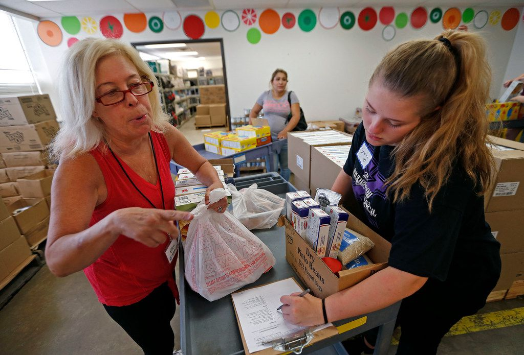Volunteers Ellen Brude (left) and Grace Dickerson, 15, gather up groceries for client Lorena Baires at Crossroads Community Services.