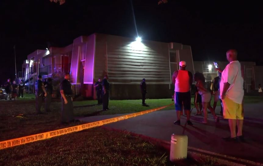 Dallas police and neighbors look things over after a man was shot and killed Thursday by a resident attempting to prevent a break-in to his apartment in east Oak Cliff.