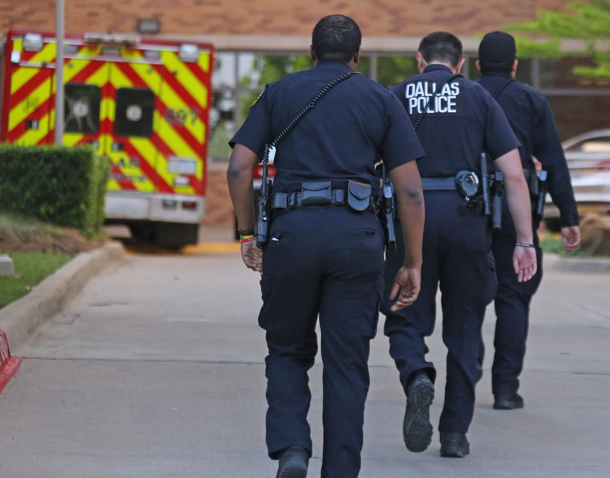 Dallas police officers walk to the entrance to the emergency room at Presbyterian Hospital in Dallas. Two Dallas policemen were reportedly shot at a nearby Home Depot and reportedly were transported to the Dallas hospital on April 24, 2018.