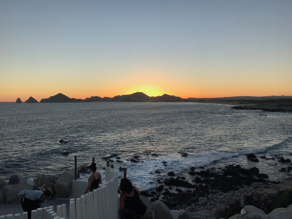 The sun sets over the beach in Cabo San Lucas, a popular destination for American tourists during spring break.