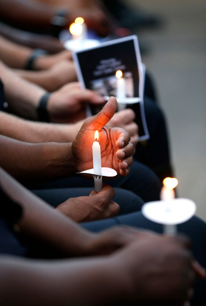 Dallas police officers hold candles during a candlelight vigil for one of their own in this photo from earlier this summer.
