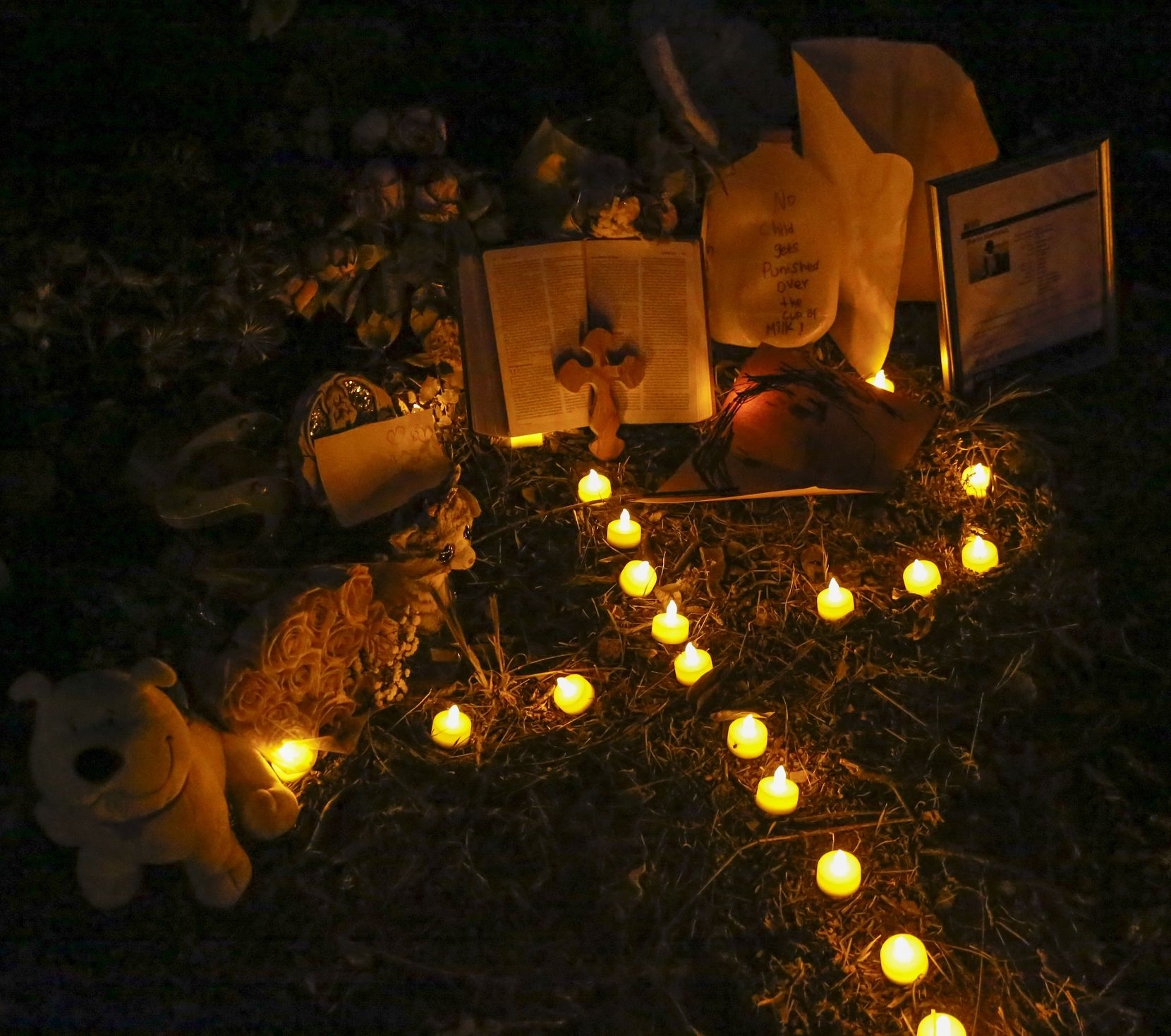 Artificial candles placed in the pattern of a cross light a small tribute set up for Sherin Mathews on Oct. 12.