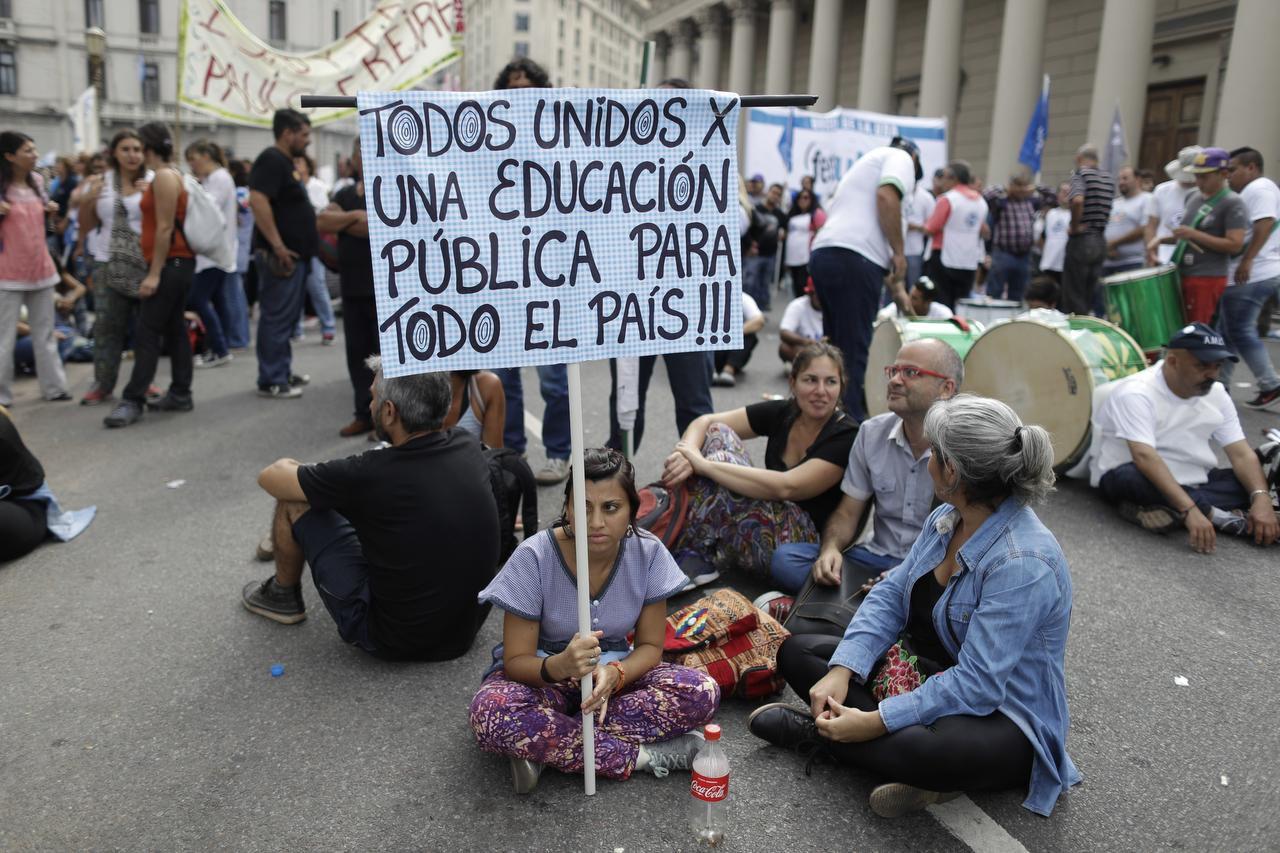 Docentes sostienen una bandera argentina durante una protesta en la que reclaman mejores salarios en Buenos Aires, Argentina, el miércoles 22 de marzo de 2017. (AP/VÍCTOR R. CAIVANO)