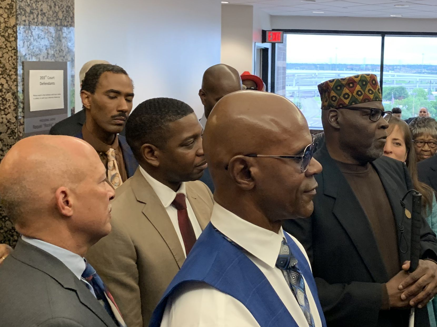 """Dennis Allen (blue vest) and Stanley Mozee (black jacket) talk with the media after state District Judge Racquel """"Rocky"""" Jones declared them """"actually innocent"""" in the 1999 murder of the Rev. Jesse Borns Jr."""