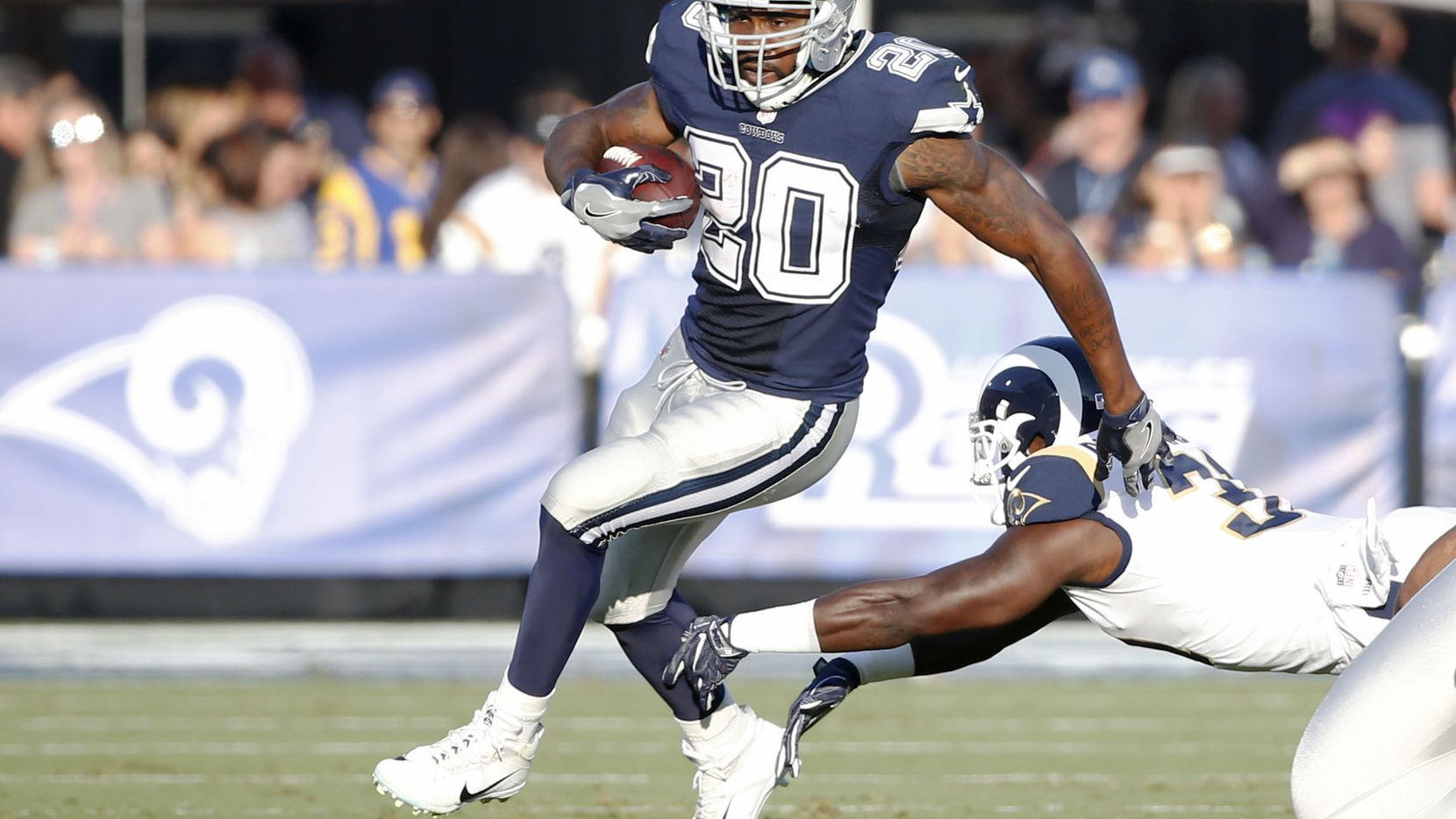Dallas Cowboys running back Darren McFadden runs past a Los Angeles Rams player during a 2017 preseason game.