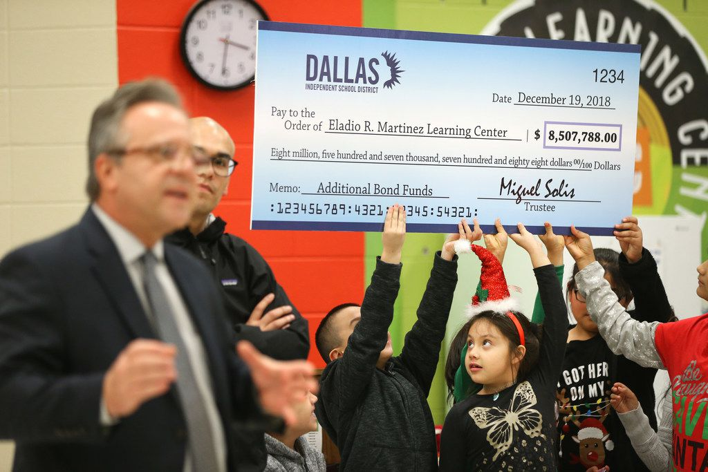 Students hold up a a check for additional bond funds to improve Eladio R. Martinez Learning Center while Scott Layne (far left), DISD's deputy superintendent of operations, helps make the announcement alongside board member Miguel Solis at the school in Dallas on Wednesday, Dec. 19, 2018.