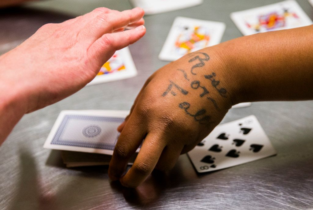 """Rise or Fall"" is tattooed on the hand of inmate Sheniqua Miller as she and Stacy Jensen play cards in their unit at Burnet County Jail. Miller had probation but violated the terms, testing positive for marijuana."