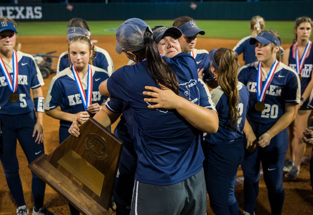 Keller pitcher Dylann Kaderka (22) hugs head coach Christina Gwyn-Barton while holding the semifinalist trophy after a 1-0 loss at a UIL Class 6A state semifinal softball game between Keller and Katy on Friday, May 31, 2019 at Red & Charline McCombs Field at the University of Texas in Austin. (Ashley Landis/The Dallas Morning News)