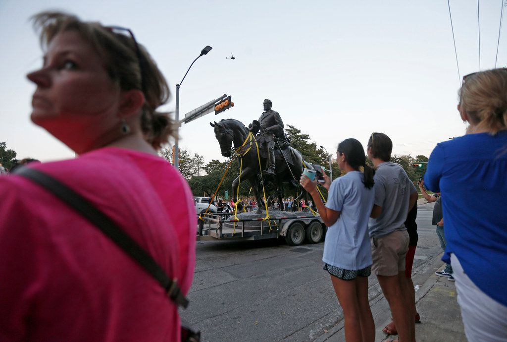 The Robert E. Lee statue is carried on a truck as people watch the statue at Robert E. Lee Park in Dallas, Thursday, Sept. 14, 2017. Crews arranged by Dallas officials removed the statue from its pedestal Thursday and carted it away from the park.