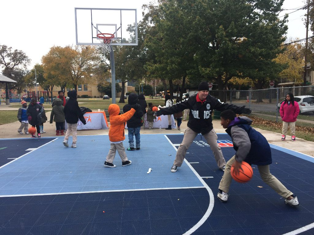 Officer Allison Brockford, who works in the Dallas Police Department's youth outreach unit, played basketball with children at the J.W. Ray park's new Dream Court  in December.  (Named Rajwani/ The Dallas Morning News)