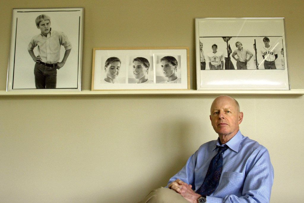 """Robert A. """"Bob"""" Wilson posed for a 2004 portrait in his Dallas office, beneath photos of his sons, Owen, Luke and Andrew Wilson.  At left is a portrait of Owen by Richard Avedon; Wilson's wife, Laura, took the pictures of Luke at center; and at right are images by Avedon of all three sons."""