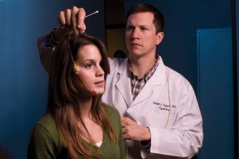 UNT sleep researcher Daniel Taylor places electrodes on the head of a student at the university's Sleep Research Laboratory