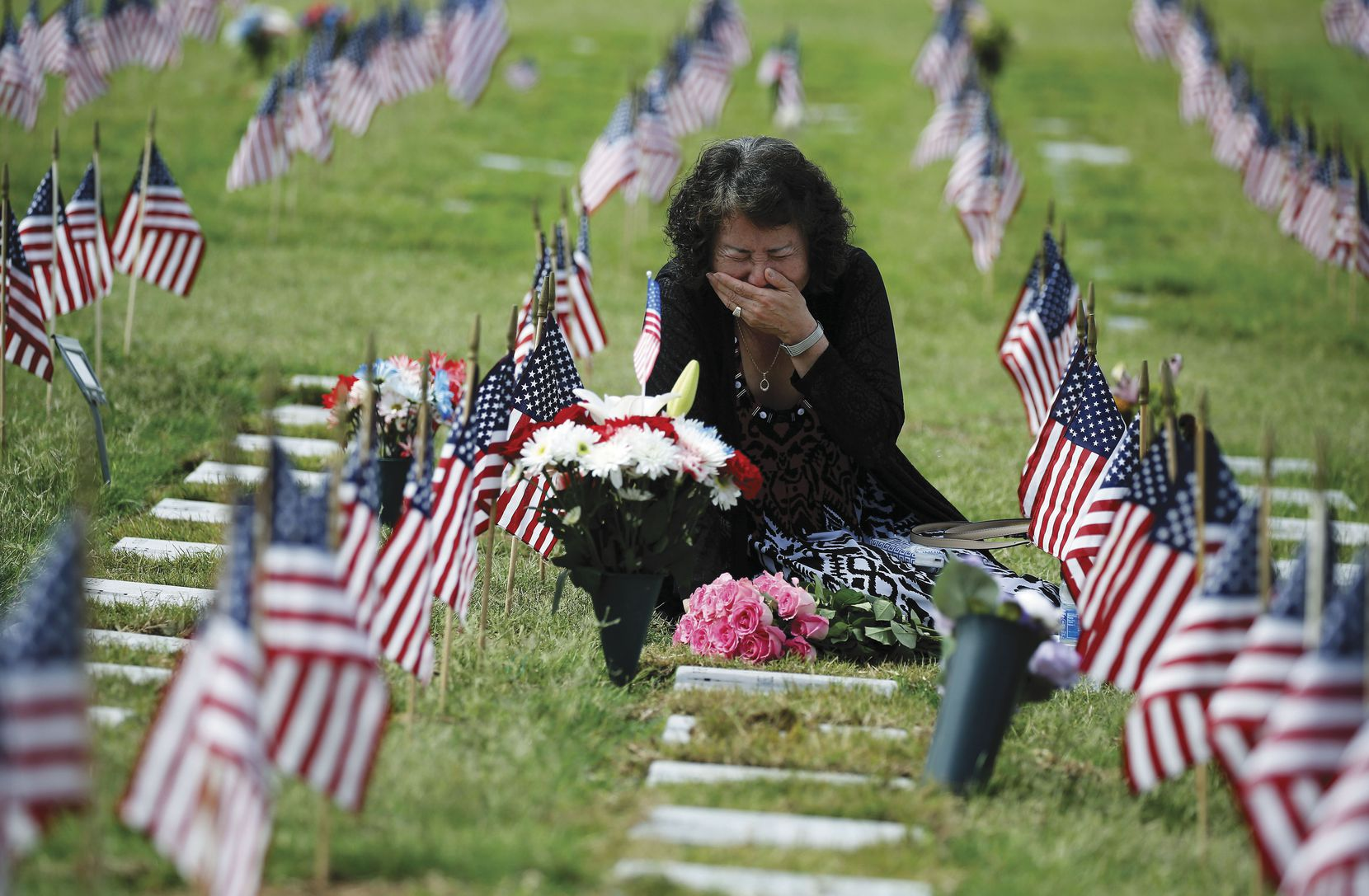Una Pemberton of Wichita Falls weeps at the grave of her son, Clem J. Strait III, who served in the Army in the Persian Gulf War. She was there to honor him during the Memorial Day observance at D-FW National Cemetery.