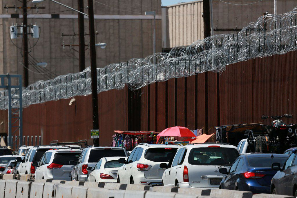 Motorists wait in line to cross the border into Calexico, Calif.