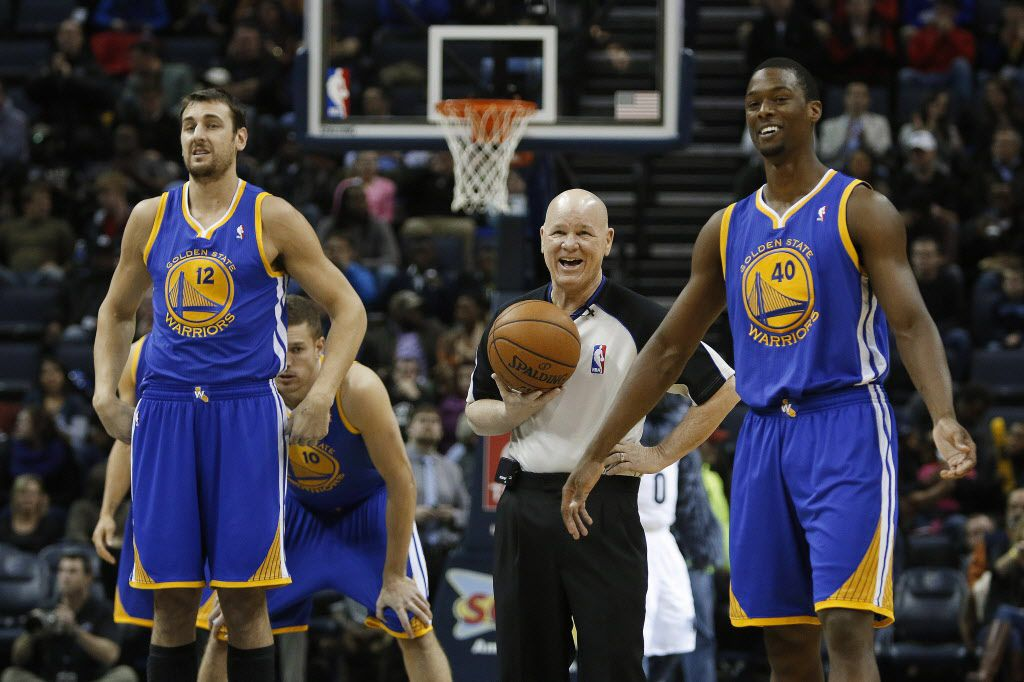 A referee jokes with Golden State Warriors center Andrew Bogut (12), of Australia, and forward Harrison Barnes (40) as they wait to tip off against the Memphis Grizzlies in an NBA basketball game Saturday, Dec. 7, 2013, in Memphis, Tenn. (AP Photo/Lance Murphey) ORG XMIT: OTK106