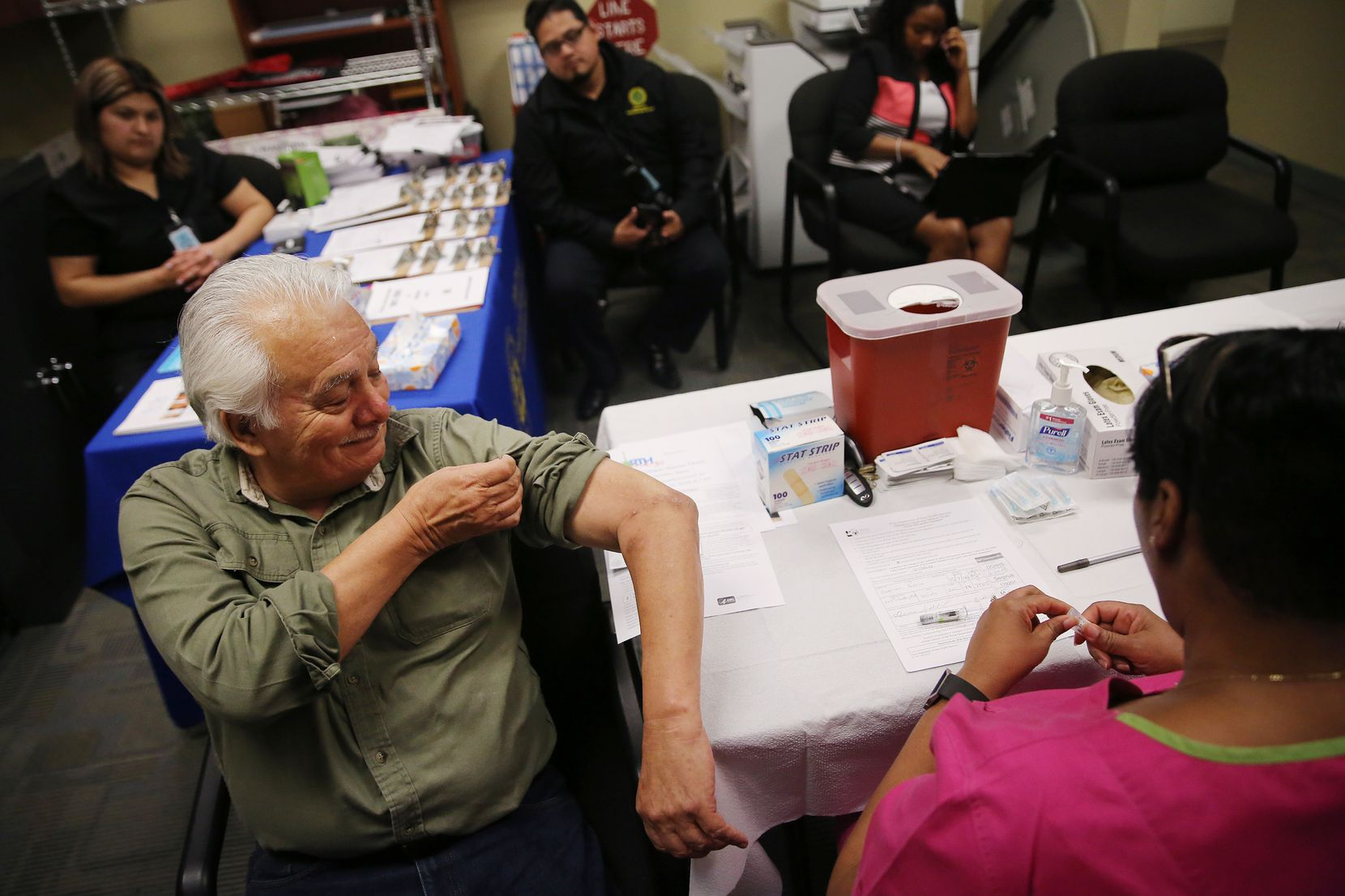 Gavino Saldivar, of DeSoto, Texas, lifts his sleeve up before receiving an influenza vaccine from Barbara Davis (right), a registered nurse, at a mobile immunization clinic hosted by Dallas County Health and Human Services at the DeSoto Senior Center in DeSoto Tuesday February 20, 2018. According to Renae Crutchfield, public information officer for Dallas County Health and Human Services, the county was focusing on reaching the elderly since that population is the most vulnerable to the influenza.