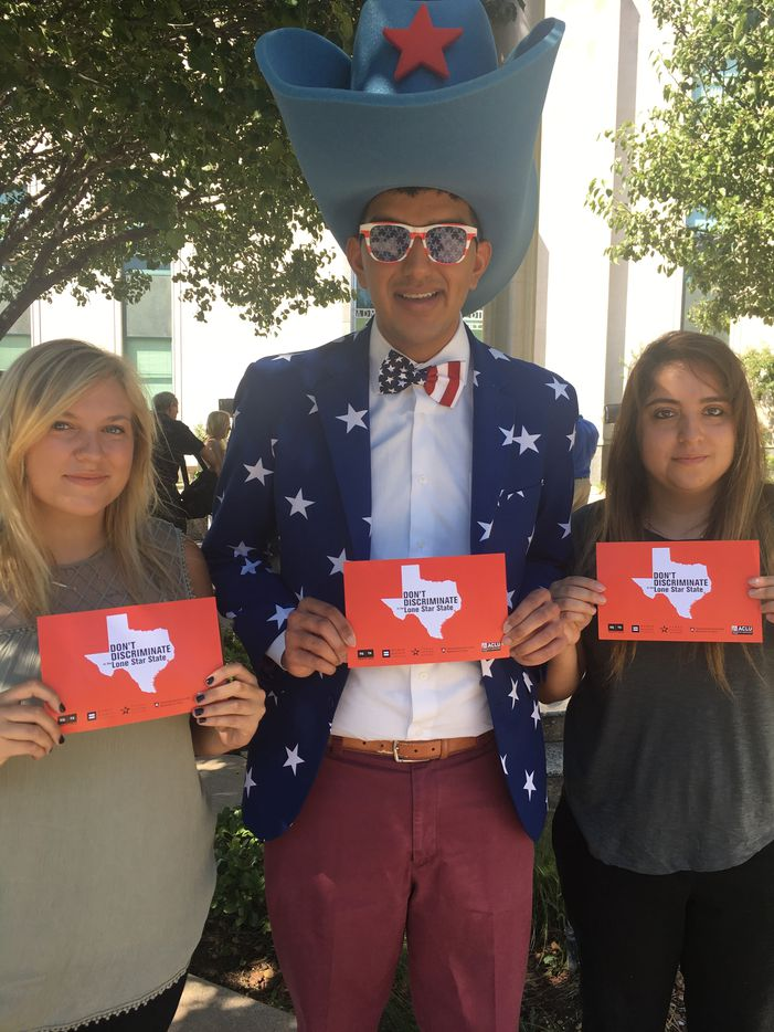 From left: Dallas community members Tessa McGlynn, Bhavik Patel and Carmen Ayala attended the rally. with signs.