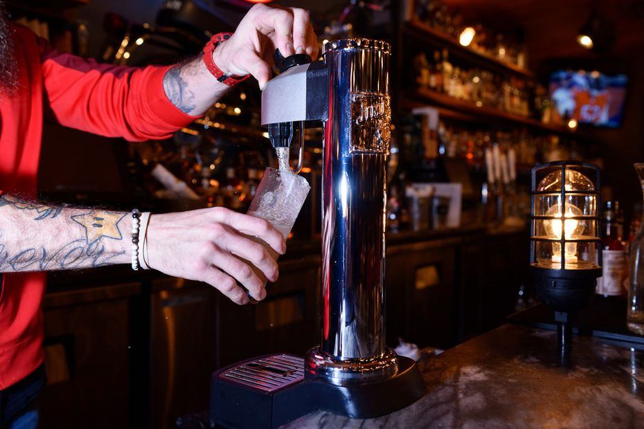 Bar manager Kris Johnson, left, pours a Japanese Highball from a Jim Beam Black Highball machine at Town Hearth in Dallas.