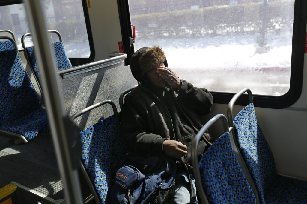 Artis Frank rubs his face while riding a DART bus during the last leg of his long daily commute between his home in southeast Dallas and his job in Irving. (2015 File Photo/Nathan Hunsinger)