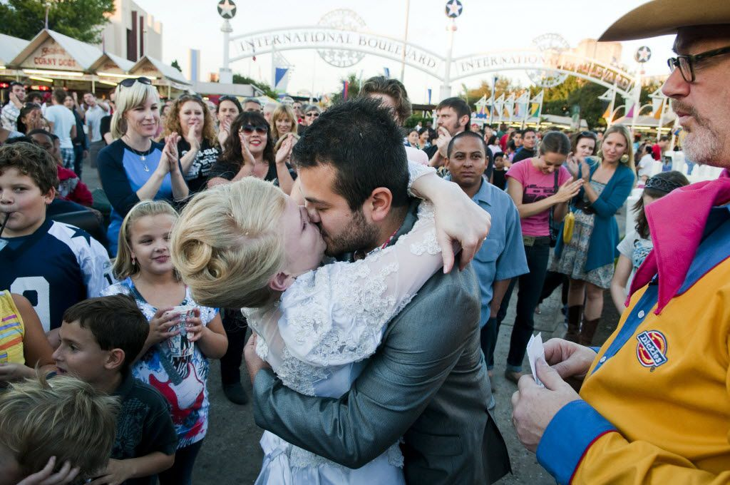 """Sara Rice of Dallas kisses her husband Jose Luis Martinez Hernandez of Mexico City after their friend Tom """"Pinky Diablo"""" Sale of Ennis conducted their wedding ceremony in front of Big Tex at the State Fair of Texas on Oct. 12, 2010."""