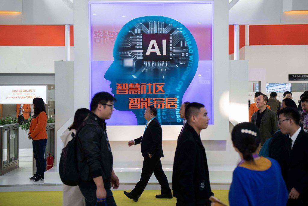Visitors walk past a stand with artificial inteligence security cameras using facial recognition technology at the 14th China International Exhibition on Public Safety and Security at the China International Exhibition Center in Beijing on Oct. 24, 2018