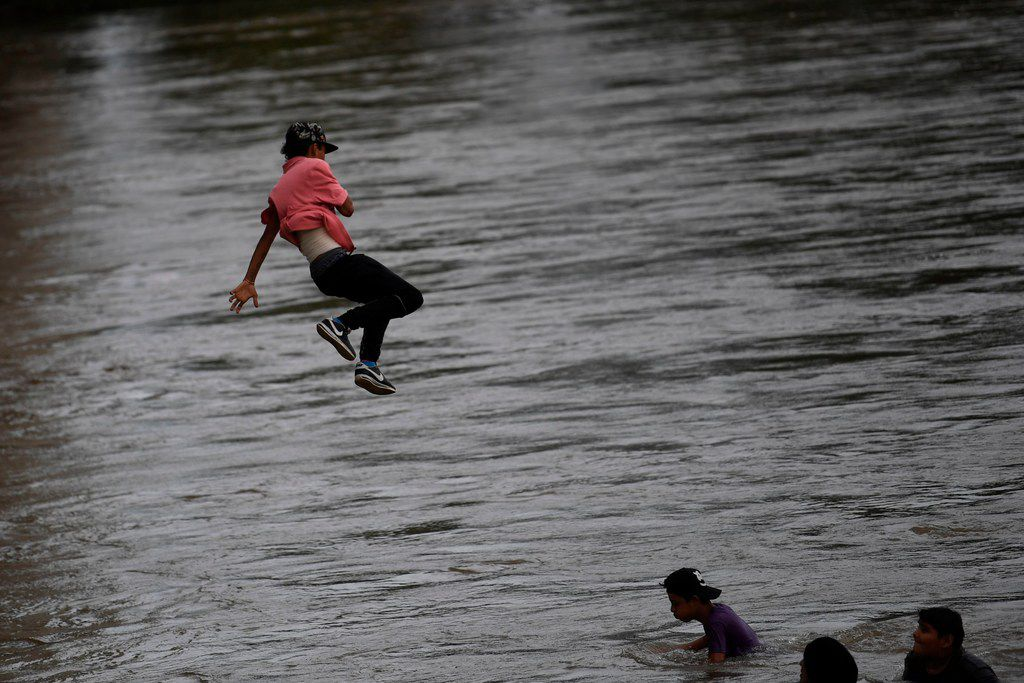 A Honduran migrant jumps from the Guatemala-Mexico international border bridge into the Suchiate river, to swim or board a raft and reach Mexico in Ciudad Hidalgo, Chiapas state, Mexico, on October 19, 2018.